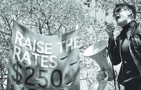 "Photograph: Protester and ""Raise the Rates"" banner"